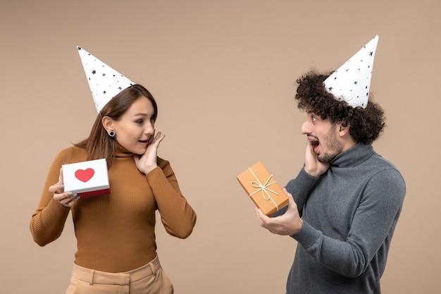 Nieuwjaar fotograferen met jong koppel dragen nieuwjaarshoed meisje met hart en man met cadeau op grijs