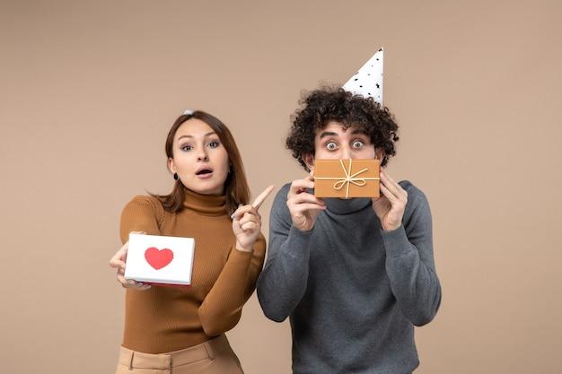 Nieuwjaar fotograferen met jong koppel dragen nieuwjaarshoed meisje met hart en wijzend geschenk in de hand van man op grijs