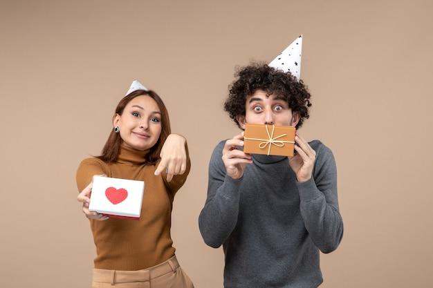 Nieuwjaar fotograferen met jong koppel dragen nieuwjaarshoed meisje wijzend hart en man met cadeau op grijs