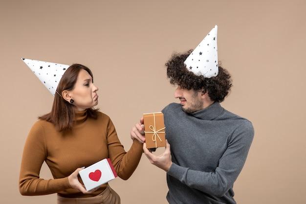 Nieuwjaar fotograferen met jong koppel dragen nieuwjaarshoed nerveus meisje met hart en verwarde man met cadeau op grijs