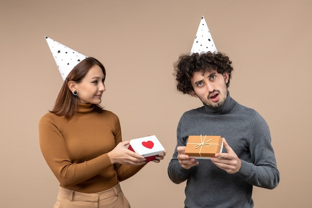 Nieuwjaar fotograferen met jong koppel dragen nieuwjaarshoed romantisch meisje met hart en man met cadeau op grijs