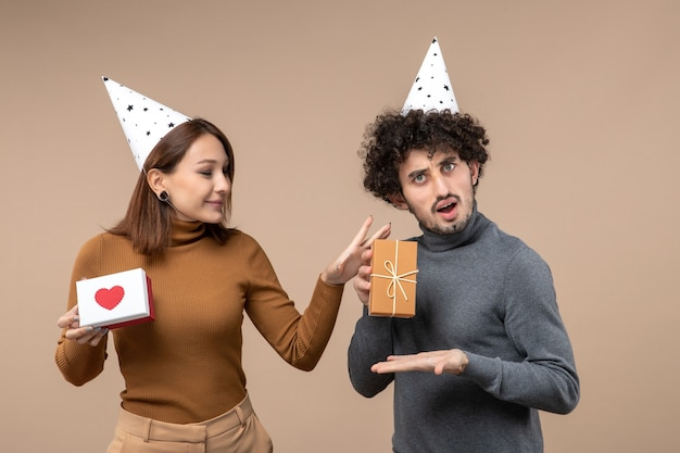 Nieuwjaar fotograferen met verrast jong koppel draagt nieuwjaarshoed meisje met hart en man met cadeau op grijs