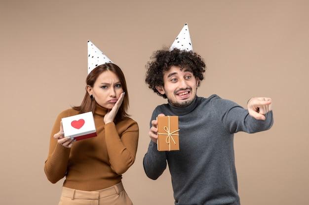 Nieuwjaar fotograferen met verward jong stel draagt nieuwjaarshoed meisje met hart en man met cadeau op grijs