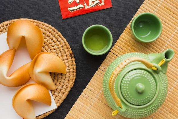 Nieuwjaar gelukskoekjes en set van groene theepot en kopjes