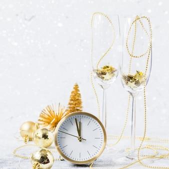 Nieuwjaar. gouden decoratie met klok, ballen, boom en glazen bekers