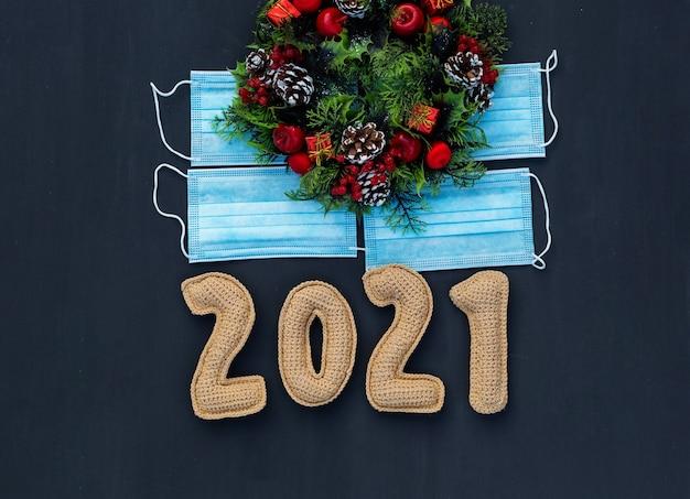 Nieuwjaar in de context van coronavirus gebreide nummers 2021 op medisch masker op krijtbord