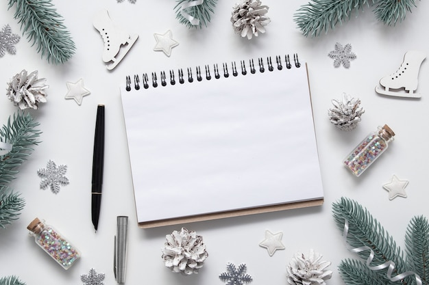 Nieuwjaar kerst plat lag met lege notebook kopie ruimte sterren sneeuwvlokken en feestelijk decor op witte achtergrond