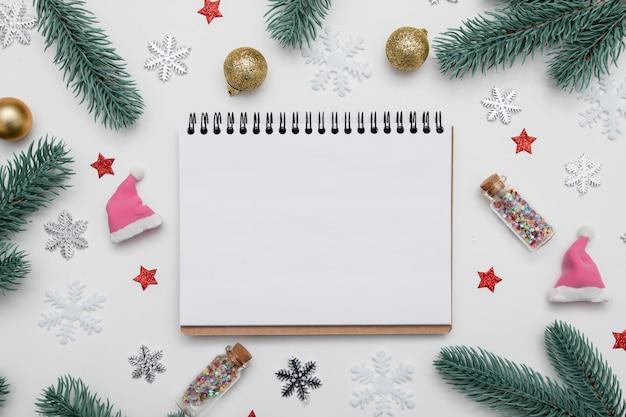 Nieuwjaar kerst plat lag met lege notebook kopie ruimte, sterren, sneeuwvlokken en feestelijk decor op witte achtergrond