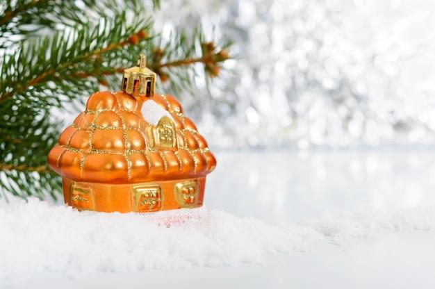 Nieuwjaar, kerst wenskaart. klein decoratief huis in de sneeuw -