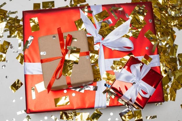 Nieuwjaar kerstcadeautjes met linten, gouden confetti, bovenaanzicht. kerstvakantie 2021 viering. feestelijke geschenkdozen.