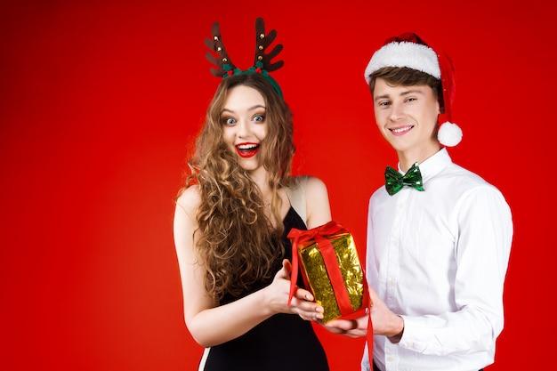 Nieuwjaar kerstfeest concept gelukkig plezier lachende vrienden paar dragen sprookje carnaval kostuum santa claus herten hoed geven huidige verrassing vieren wintervakantie geïsoleerd