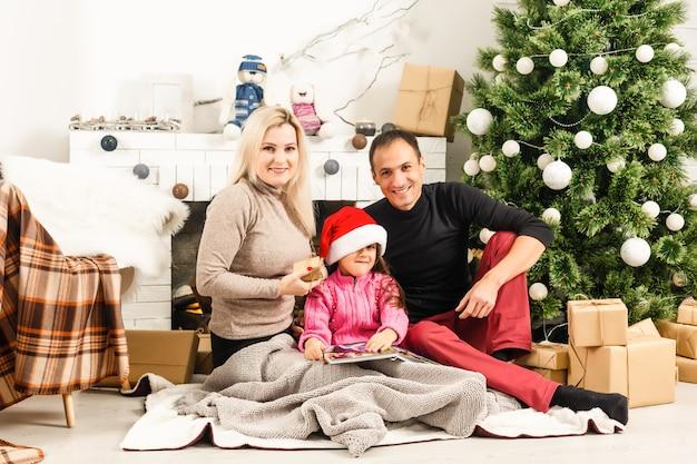 Nieuwjaar. kerstmis. familie. jonge ouders en hun dochtertje in kerstmutsen brengen samen tijd door in de buurt van de kerstboom