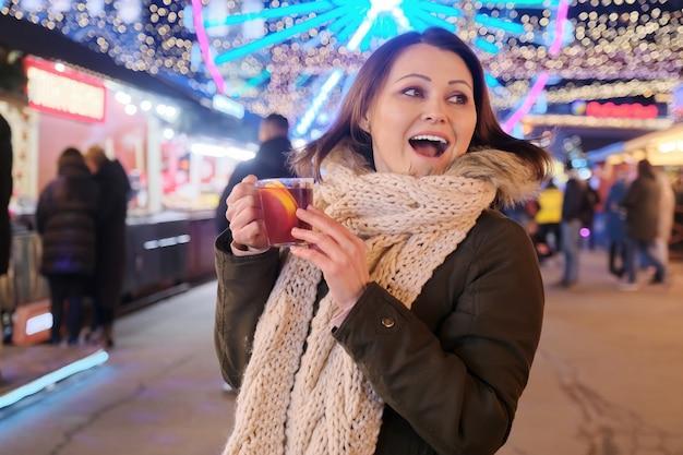 Nieuwjaar, kerstmis, feestelijke avondmarkt in de stad, rijpe gelukkige vrouw met een mok glühwein.