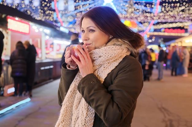 Nieuwjaar, kerstmis, feestelijke avondmarkt in de stad, rijpe gelukkige vrouw met een mok glühwein