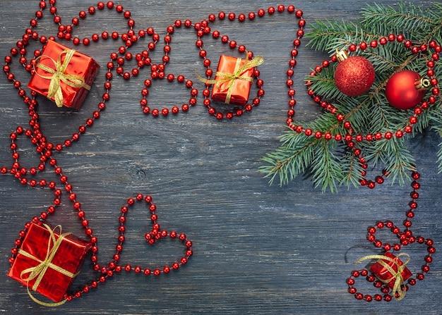 Nieuwjaar kerstmis. poot van sparren, kerstballen, cadeau, kralen, hart op een oud, armoedig, donker houten oppervlak