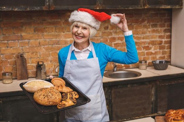 Nieuwjaar koken. het portret van aantrekkelijke hogere oude vrouw kookt op keuken. grootmoeder die smakelijk kerstmisbaksel maakt.
