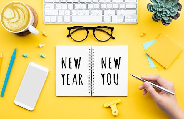 Nieuwjaar nieuw u concepten met persoon die tekst op briefpapier schrijft.