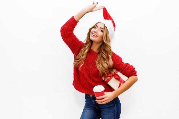 Nieuwjaar of kerstavond. blond aantrekkelijk meisje in de dozen van de de holdingsgift van de maskeradehoed vrolijke stemming.