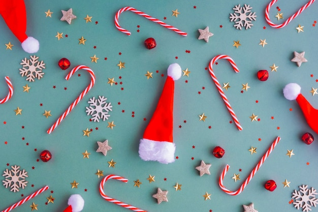 Nieuwjaar of kerstmis achtergrond. platte lei van kerstmutsen en kerstspeelgoed en lolly's