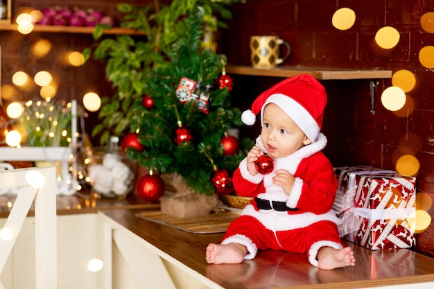 Nieuwjaar of kerstmis, een baby in een donkere keuken thuis bij de kerstboom in een pak en een kerstmanhoed die speelt met een kerstbal