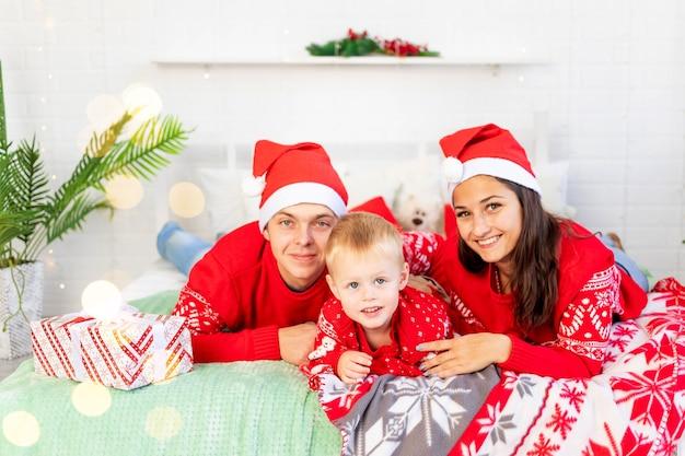 Nieuwjaar of kerstmis, een gelukkig gezin met een kind op het bed thuis bij de kerstboom in rode truien glimlachen, knuffelen en zoenen feliciteren met de vakantie