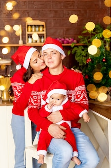 Nieuwjaar of kerstmis, een gelukkige jonge familie moeder, vader en baby in de donkere keuken van het huis met een kerstboom in rode truien en kerstman hoeden glimlachend, knuffelen feliciteren met de vakantie