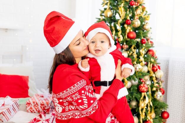 Nieuwjaar of kerstmis, een jonge moeder met een baby op het bed thuis bij de kerstboom in een kerstmankostuum knuffelend en wachtend op de vakantie glimlachend
