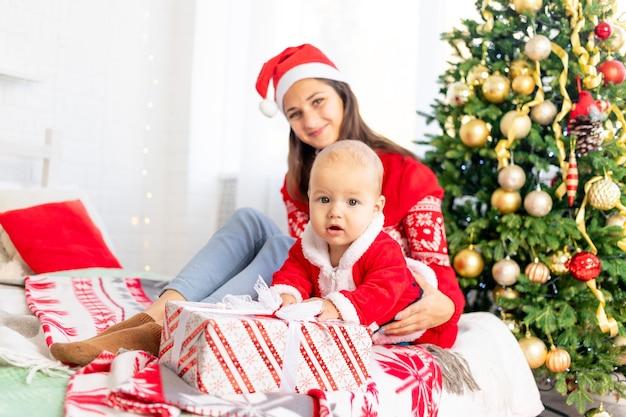 Nieuwjaar of kerstmis, een jonge moeder met een baby opent een cadeau op het bed thuis bij de kerstboom in een kerstmankostuum knuffelend en wachtend op de vakantie glimlachend