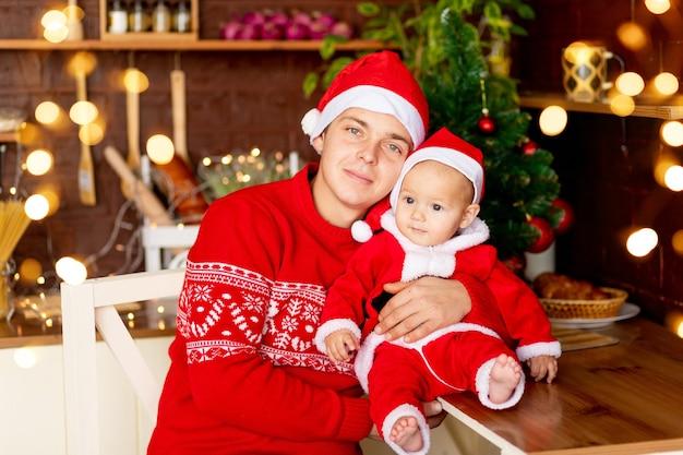 Nieuwjaar of kerstmis, een vader met een baby in een rode trui en een kerstmanhoed in de keuken, een gelukkig jong gezin bij de kerstboom glimlachend, knuffelend