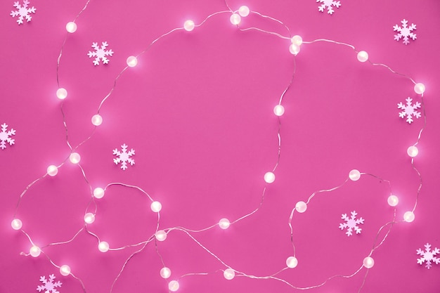Nieuwjaar of kerstmis patroon plat lag bovenaanzicht xmas vakantie feest decoratieve papier sneeuwvlokken en slinger van feestelijke verlichting op roze achtergrond. trendy levendige zwart-wit getinte achtergrond.