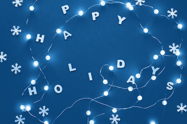 Nieuwjaar of kerstmis patroon plat lag xmas vakantie viering decoratief papier sneeuwvlokken en slinger van feestelijke lichten op blauw papier. trendy c; assic blauwe monochrome getinte achtergrond.