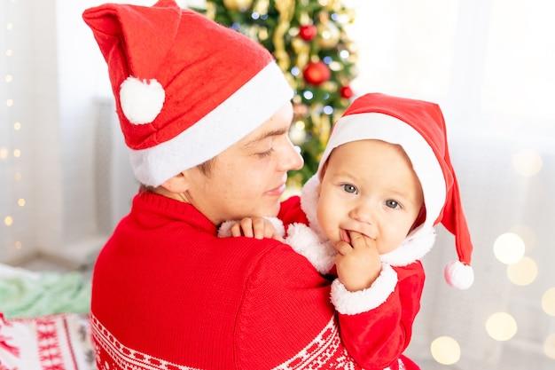Nieuwjaar of kerstmis, vader met een baby in zijn armen thuis bij de kerstboom in een kerstmankostuum en een hoed die lacht, knuffelt en wacht op de vakantie