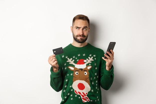 Nieuwjaar online winkelen en kerstconcept doordachte man met behulp van mobiele telefoon en creditcard thi...