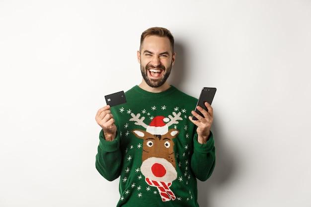 Nieuwjaar, online winkelen en kerstconcept. opgewonden man met creditcard en smartphone, staande op een witte achtergrond