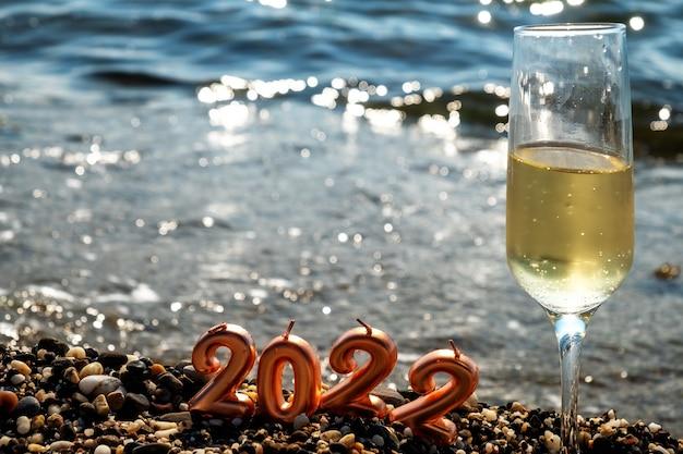 Nieuwjaar op het strand. de cijfers van het nieuwe jaar 2022 zitten vast in het zand aan de oevers van de blauwe zee. nieuwjaar vakantie concept.