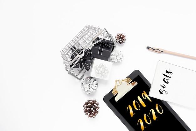 Nieuwjaar op zwart klembord met blanco papier, geschenkdoos en dennenappels