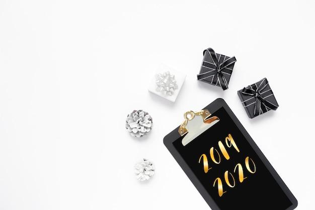 Nieuwjaar op zwart klembord met geschenkdozen