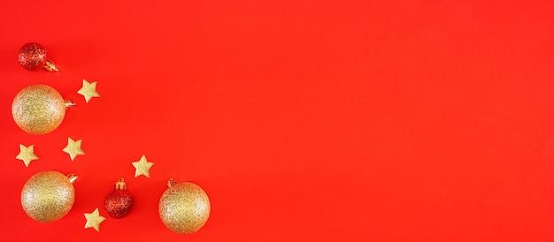 Nieuwjaar plat lag. glanzende gouden en rode kerstballen en sterren op een heldere rode feestelijke achtergrond.