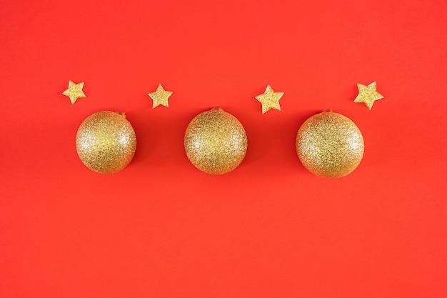 Nieuwjaar plat lag. glanzende gouden kerstballen en sterren op een heldere rode feestelijke achtergrond.