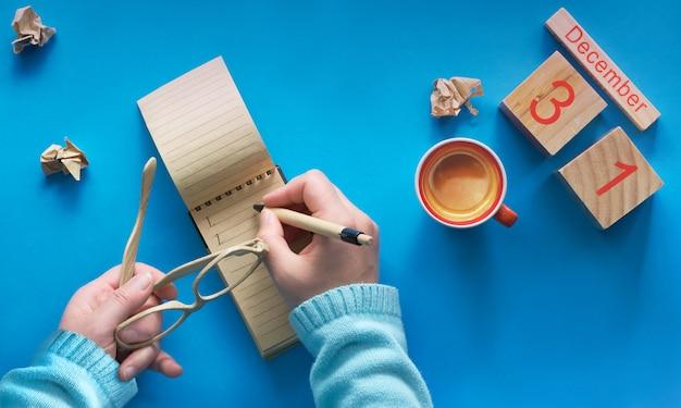 Nieuwjaar resoluties concept, hand met koffie, laptop, houten kalender en koffie op blauw