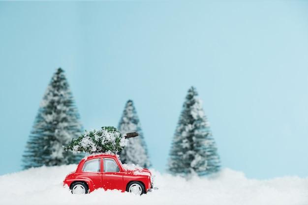 Nieuwjaar rode auto met kerstboom in besneeuwde bossen. gelukkig nieuwjaarskaart