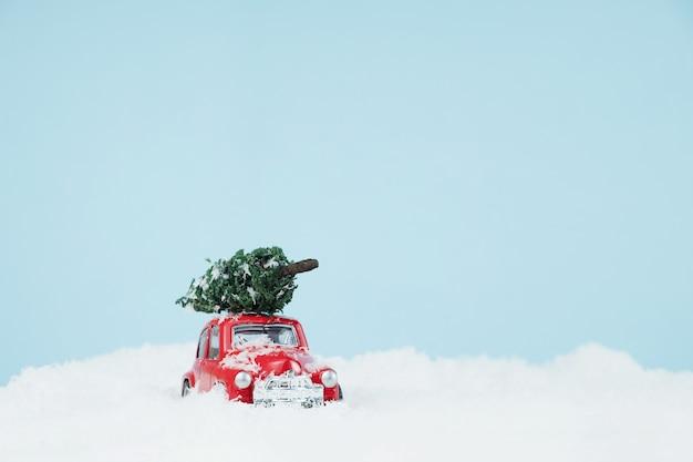 Nieuwjaar rode auto met kerstboom in een sneeuwlandschap
