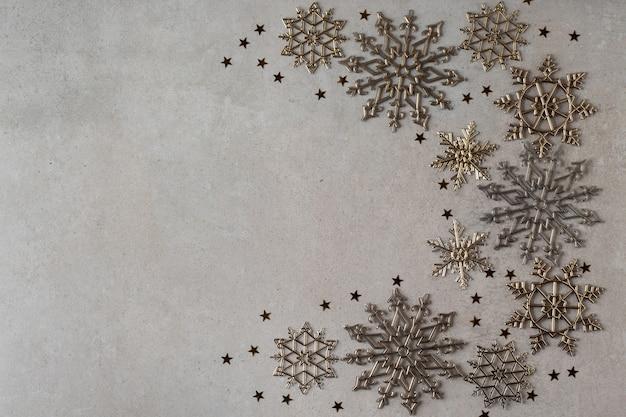 Nieuwjaar samenstelling van gouden sneeuwvlokken op grijze achtergrond plat leggen