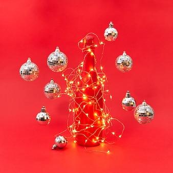 Nieuwjaar scheen lichtsnoer op een creatief geschilderde wijnfles en zwevende ballen rond op een rode achtergrond met kopieerruimte. kerst felicitatie kaart.