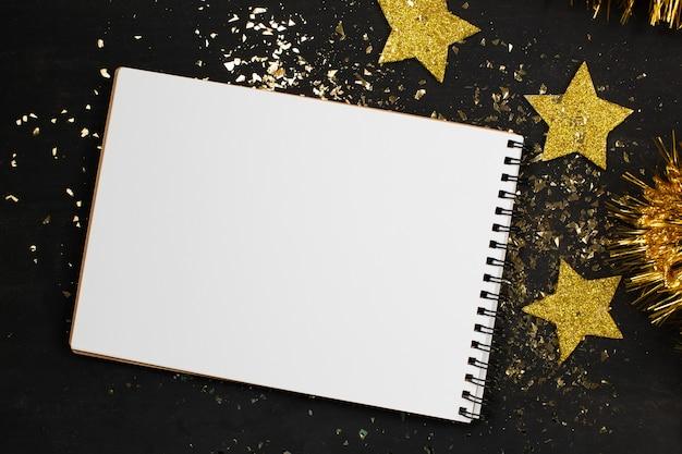 Nieuwjaar . schetsboek, gouden ster, glitter op een zwarte achtergrond.