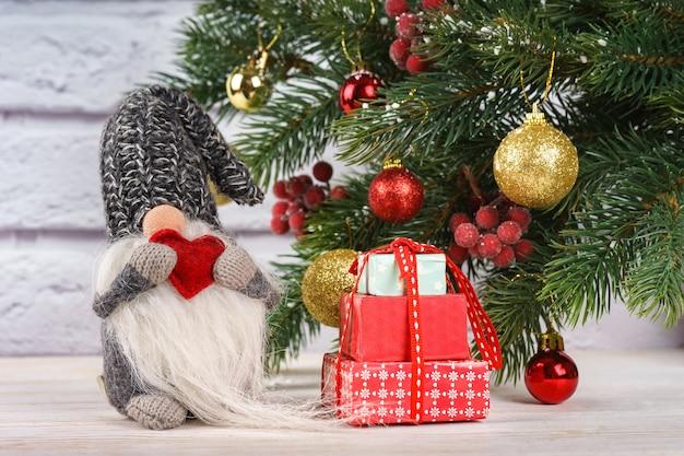 Nieuwjaar speelgoed kerstman houdt rood vorm hart op versierde kerstboom achtergrond en witte bakstenen muur.