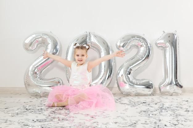Nieuwjaar, vakantie en feest concept - kleine kind meisje zit in de buurt met nummers ballonnen
