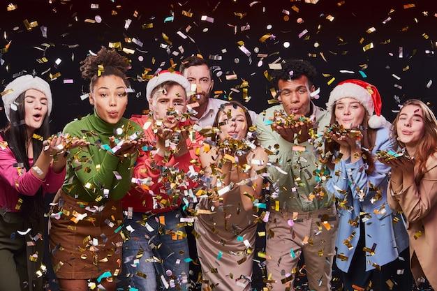 Nieuwjaar vieren samen groep jonge multiraciale gelukkige mensen die kleurrijke confetti blazen