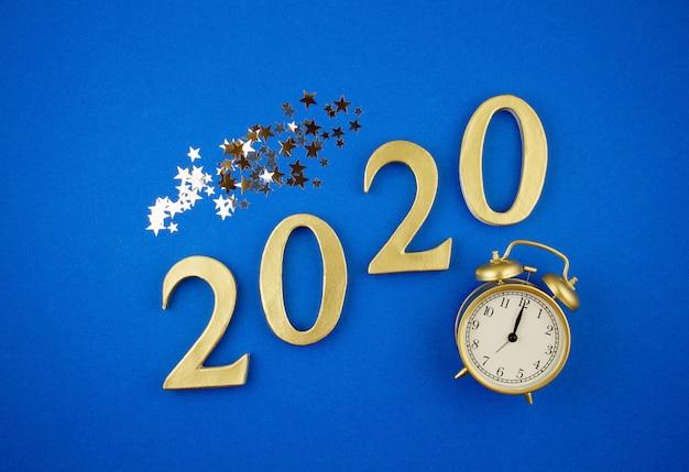 Nieuwjaar viering concept met gouden wekker en confetti op blauwe achtergrond