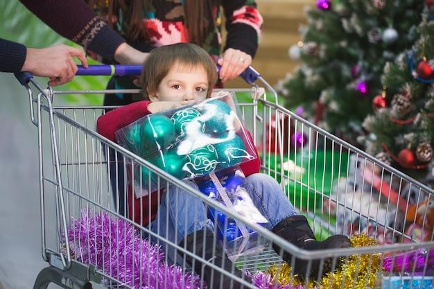Nieuwjaar winkelen. een kind winkelt in supermarkt met zijn ouder.